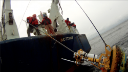Jim Ryder and John Kemp (l to r) from WHOI's Mooring Operations, Engineering & Field Support Group work from the fantail of R/V Knorr to recover a surface mooring that was part of AST2. (Credit: Ken Kostel, Woods Hole Oceanographic Institution)
