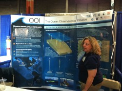 Merrie Beth Neely, OOI Science and Environmental Compliance Manager, points out the location and other facts about the Pioneer Array to visitors to the OOI booth at the 2012 Commercial Marine Expo this month. (Credit: Stephanie Murphy, Woods Hole Oceanographic Institution)