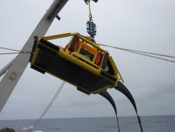 Node PN1A—the first node to be installed—shown here being launched from the back deck of the TE SubCom CS Dependable. Note the  black cable tails that curve down from the node on the right-hand side of the photo. The two ends of cable segments are spliced into the node at these tails. PN1A was deployed in deep water (2900 meters) and does not have a trawl-resistant frame.  Photo courtesy of L3-MariPro