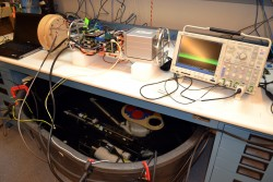 Junction Box test setup: On the bench is the open-frame prototypte of the low-power junction box. To the right is an osciloscope for signal monitoring. The junction box is connected to the three first-article instruments submerged in freshwater in the tank beneath the bench. (Photo by Mitchell Elend, University of Washington)