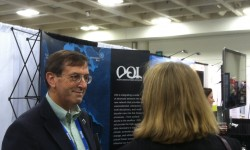 Tim Cowles, Vice President & Director of Ocean Observing at the Consortium for Ocean Leadership talks with interested conference participants at the OOI booth. (Photo Credit: OOI Communications)
