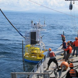 The Oregon shelf surface mooring is lowered to the water using the R/V Oceanus ship's crane. (photo courtesy of Oregon State University)