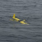 A Coastal Glider floats along the surface of the ocean. Soon it will begin its dive through the water column, sampling the water along a saw-toothed path. Gliders move by changing their buoyancy, without the use of a propeller. Credit: Craig Hayslip, OSU