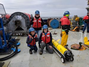 Hilary Palevsky (kneeling, right) with Wellesley students Emma Jackman (kneeling, left) and Lucy Wanzer (standing), next to one of the gliders configured for air calibration of the oxygen sensor, while preparing for deployment at the Irminger Sea Array. Photo credit: Henry Holm